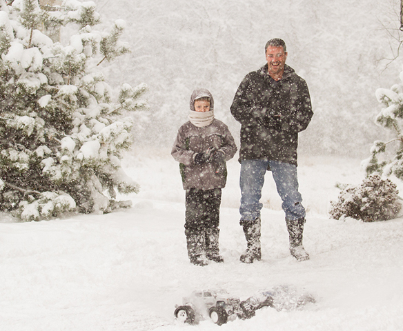 grandson and his dad driving their remote control cars in the snowstorm