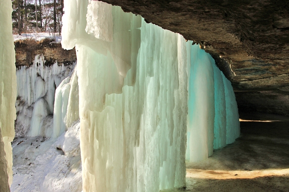 White, blue, and amber colored ice columns hang down from the cave lip, but there is 10-15 feet of ice-covered rock floor to walk on behind the ice columns.
