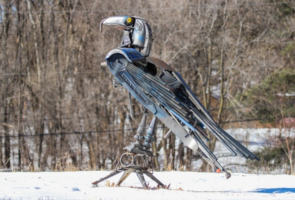 An eagle (?) metal sculpture prominently displayed in the middle of a snowy field surrounded by oaks.